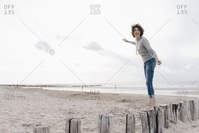Happy woman balancing on wooden stake on the beach