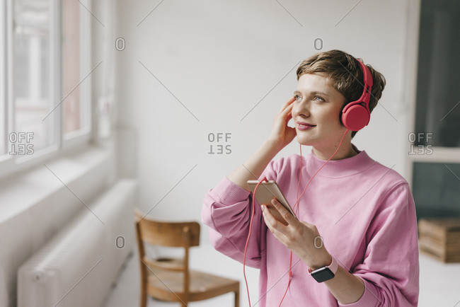 Smiling woman with cell phone and headphones listening to music