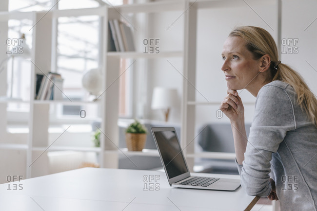 Woman with laptop sitting at desk thinking