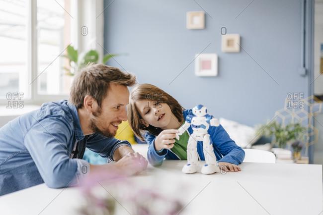 Happy father and son playing with robot on table at home