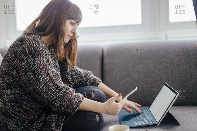 Young woman sitting on the couch using tablet and smartphone
