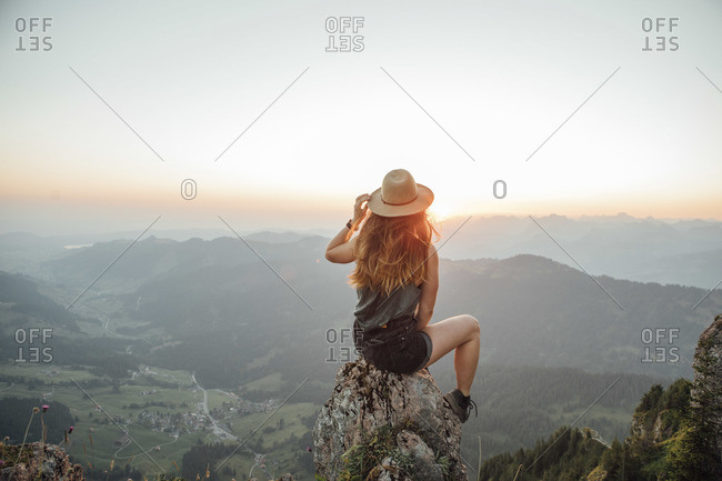 Switzerland- Grosser Mythen- young woman on a hiking trip sitting on a rock at sunrise