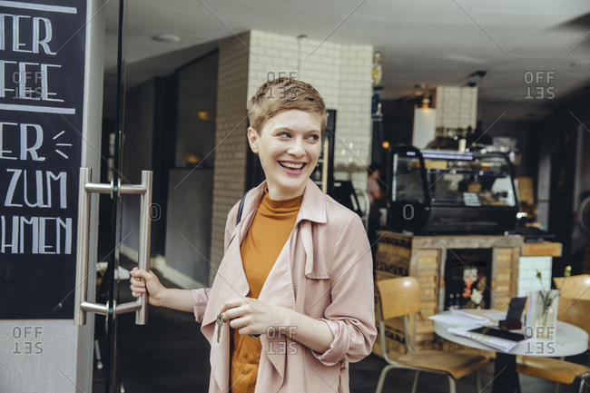 Female cafe owner unlocking the door in the morning