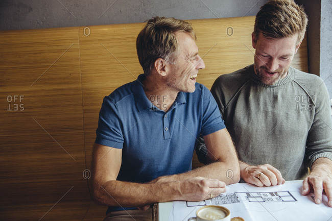 Happy gay couple looking at constructions plans for their home in cafe