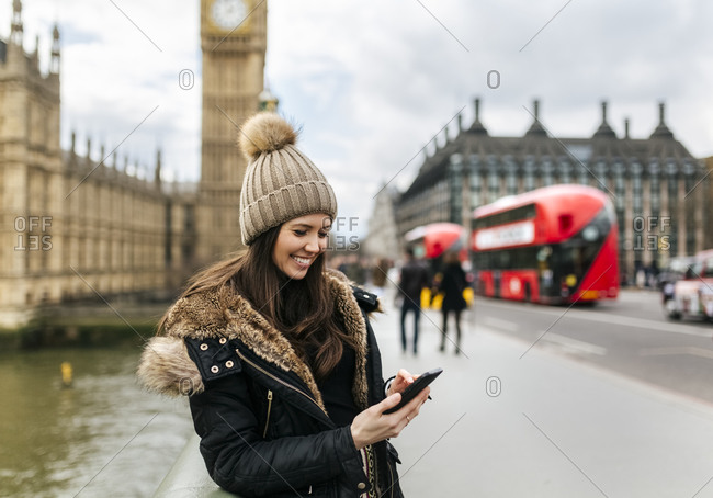 UK- London- smiling young woman looking at her smartphone in front of Palace of Westminster