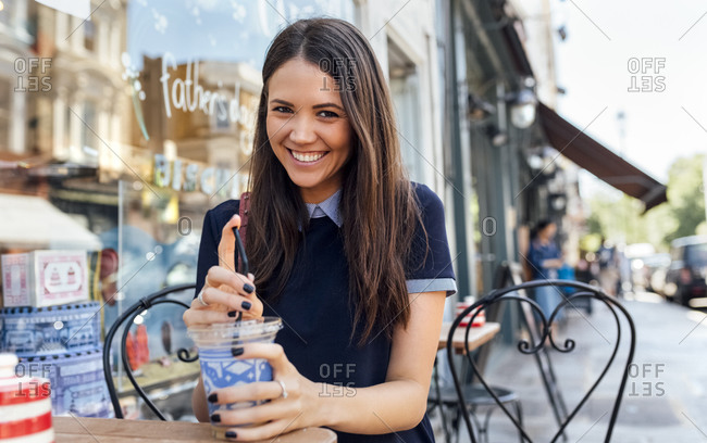 UK- London- Nottinghill- portrait of happy young woman with beverage at pavement cafe