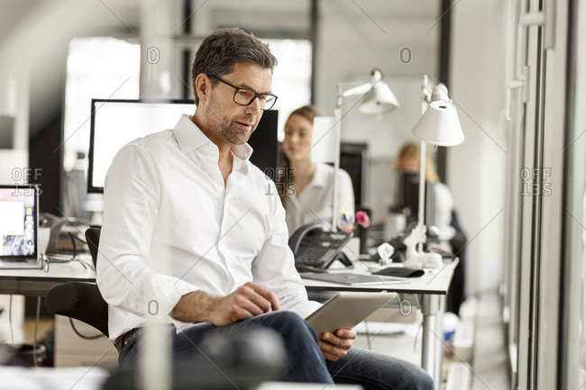 Businessman at desk in office using tablet