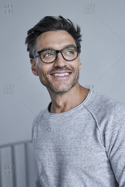 Portrait of laughing man with stubble wearing grey sweatshirt and glasses
