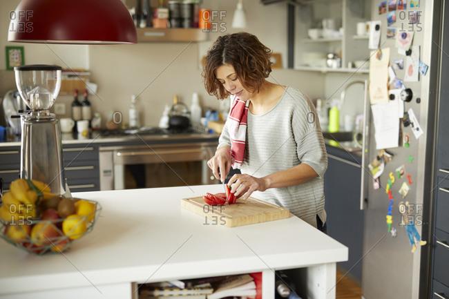 Mature woman cutting tomato in kitchen
