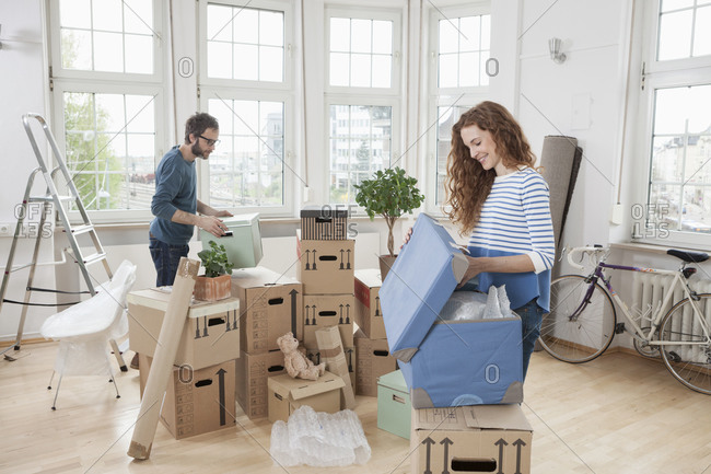 Couple in new apartment unpacking cardboard boxes