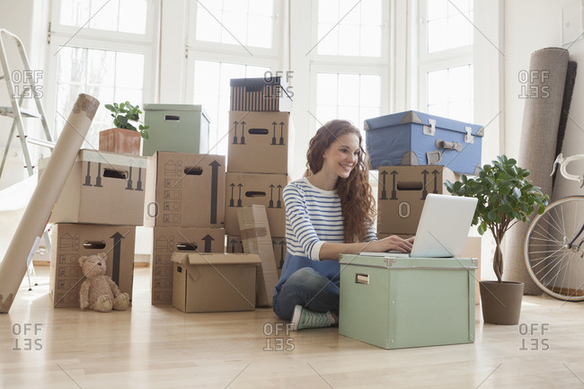 Woman surrounded by cardboard boxes using laptop