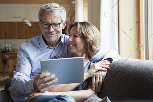 Mature couple sharing digital tablet on couch