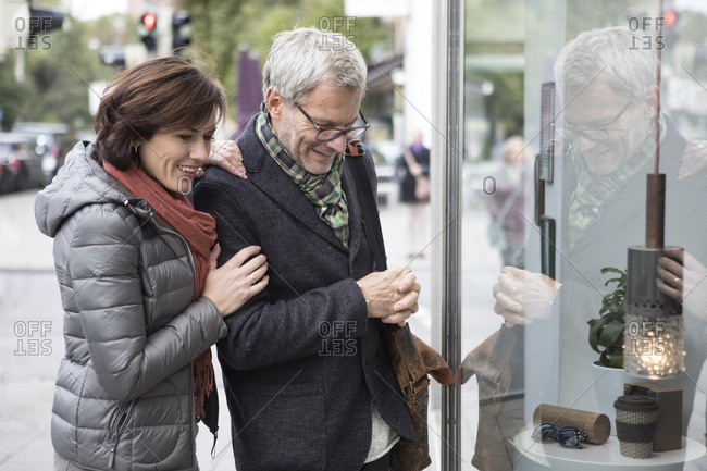 Smiling mature couple looking in shop window