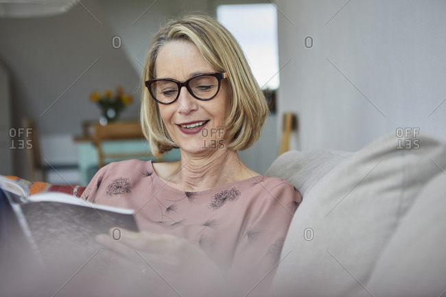 Smiling mature woman at home on the sofa reading a book