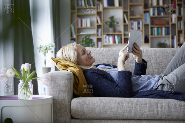 Woman using digital tablet- relaxing on couch