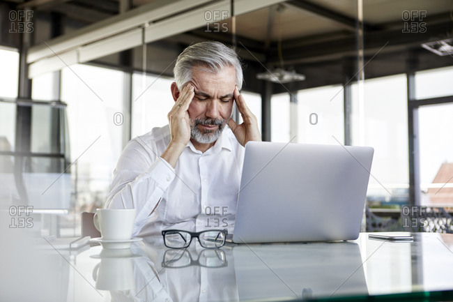 Businessman with headaches sitting at desk in office