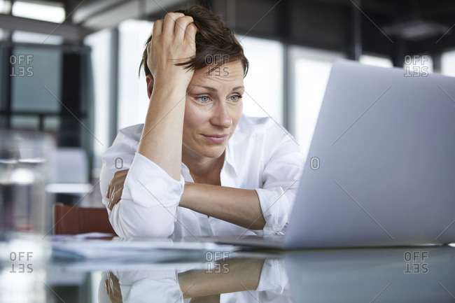 Frustrated businesswoman sitting at glass table in office looking at laptop