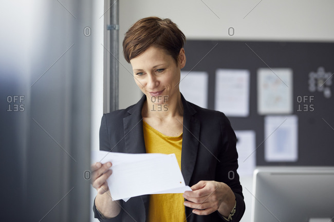 Attractive businesswoman standing in office- reading document