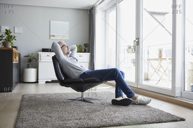 Mature man relaxing on leather chair in his living room
