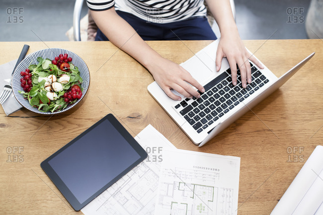 Woman at desk using laptop next to construction plan and salad