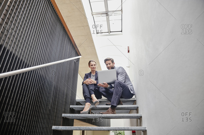 Businessman and businesswoman sitting on stairs in office sharing laptop