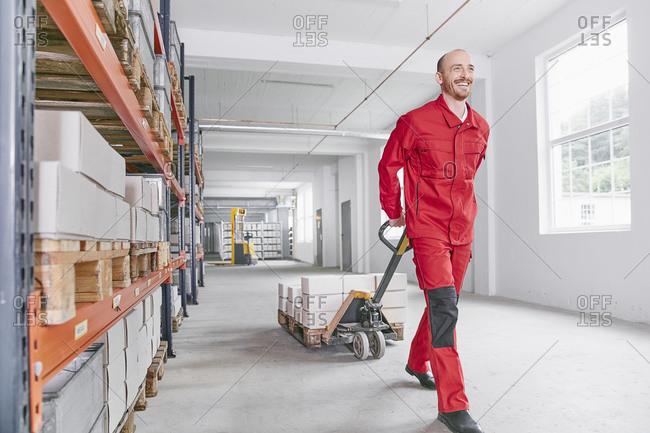 Smiling man in warehouse pulling pallet jack