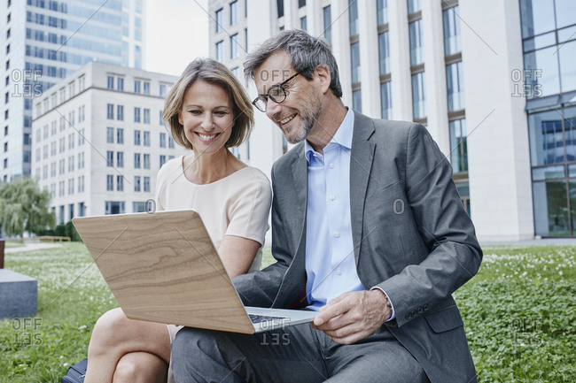 Smiling businesswoman and businessman sharing laptop outdoors