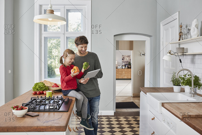 Smiling father and daughter with bell pepper and tablet in kitchen