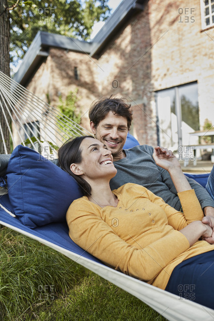 Happy couple lying in hammock in garden of their home