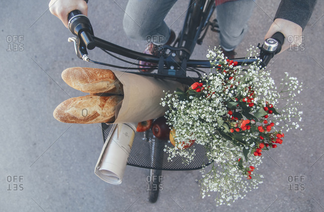 Man with apples- bouquet of flowers- newspaper and baguettes in bicycle basket