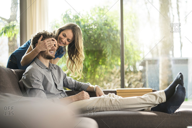 Smiling woman covering her boyfriend's eyes on sofa at home