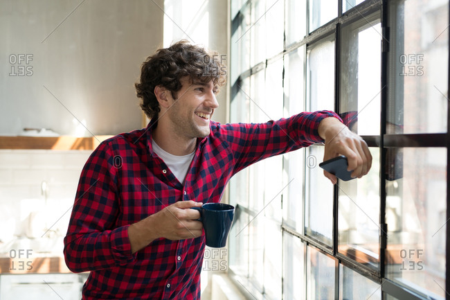Young entrepreneur standing in company kitchen- drinking coffee