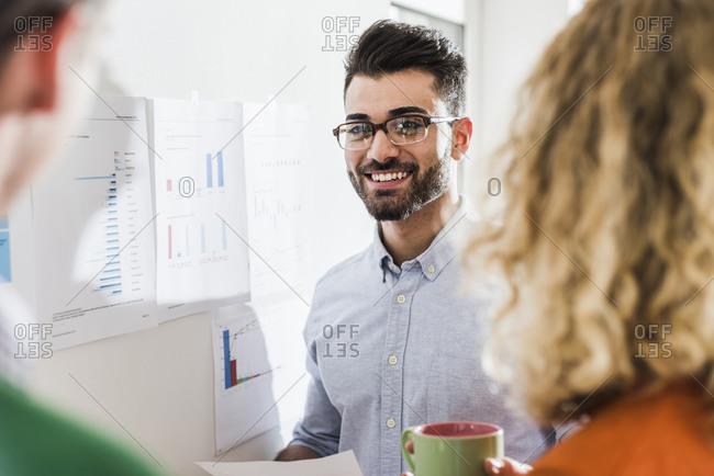 Smiling businessman with colleagues analyzing data