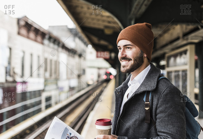 Young man waiting at metro station platform- holding disposable cup