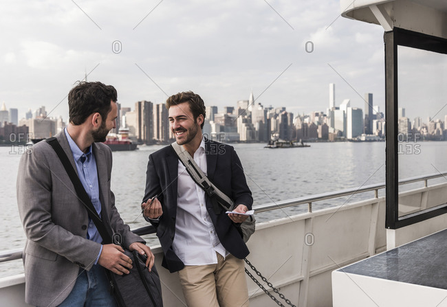 USA- New York City- two smiling businessmen talking on ferry on East River
