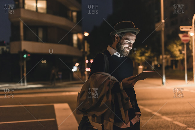 Stylish young man with tablet on urban street at night