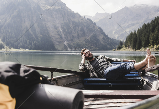 Austria- Tyrol- Alps- relaxed man in boat on mountain lake