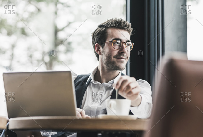 Smiling young man in a cafe with laptop and cup of coffee