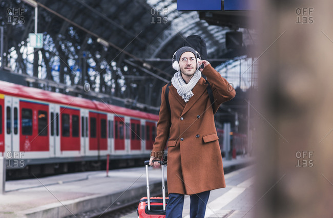 Young man with guitar case and headphones at station platform