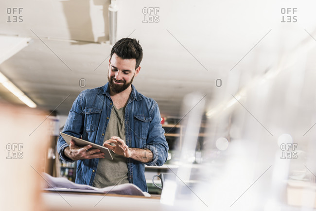 Smiling man with tablet and draft in workshop
