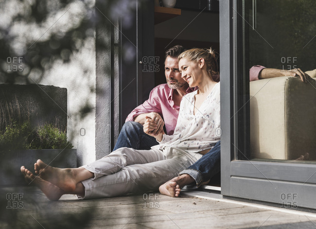 Content mature couple relaxing together at open terrace door