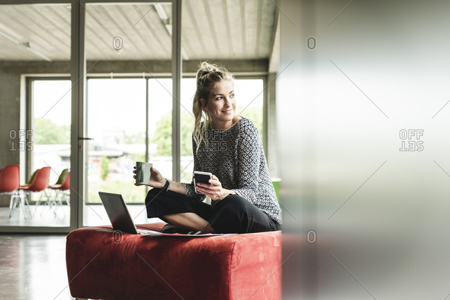 young businesswoman working in modern office- sitting on stool- using laptop