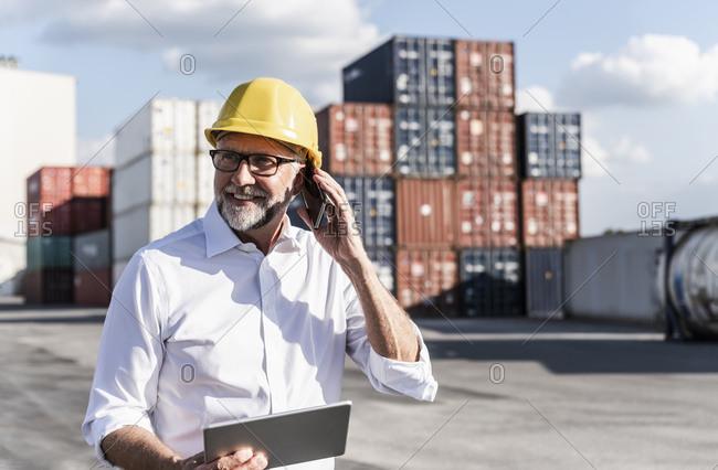 Businessman at cargo harbor- wearing safety helmet- using smartphone and digital tablet