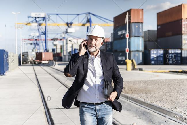 Businessman at cargo harbor- wearing safety helmet- using smartphone