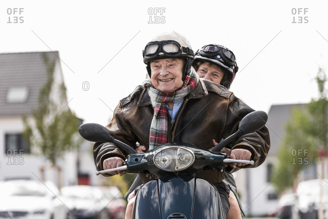 Happy senior couple riding motor scooter