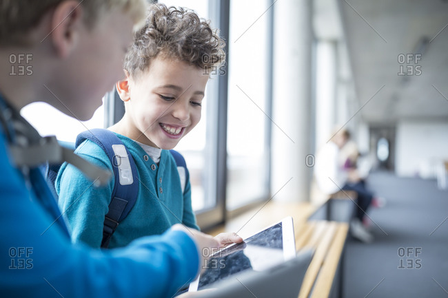 Smiling pupils sharing a tablet on school corridor