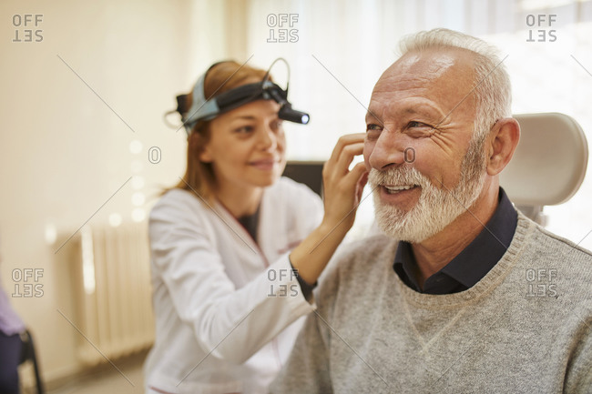 ENT physician examining ear of a senior man