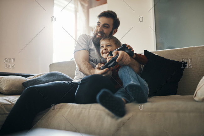 Father and son sitting together on the couch playing computer game