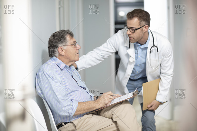 Doctor talking to patient with file in medical practice