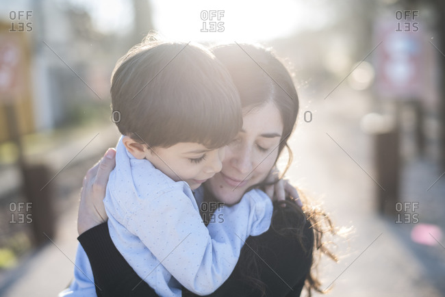 Portrait of mother and son outdoors with flare light